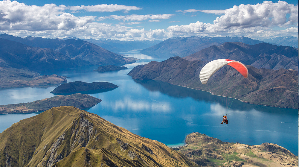 Wanaka nestles in the beautiful Southern Alps - a paraglider over Mount Roy's peak